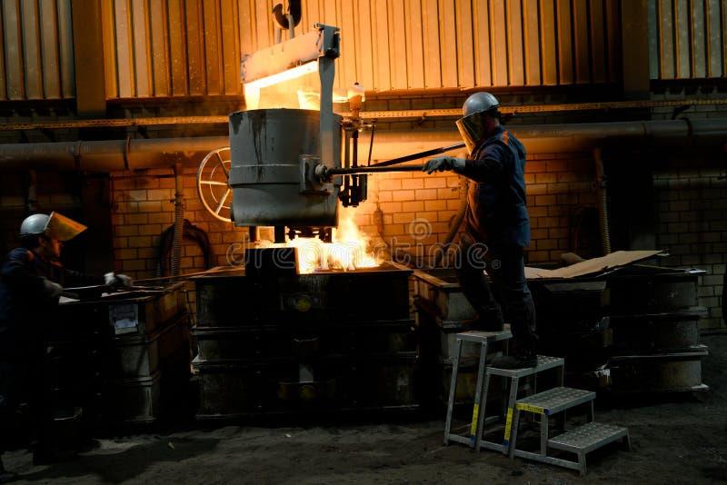 Mensen die met gloeiend gesmolten heet staal werken Staalafgietsel stock afbeelding
