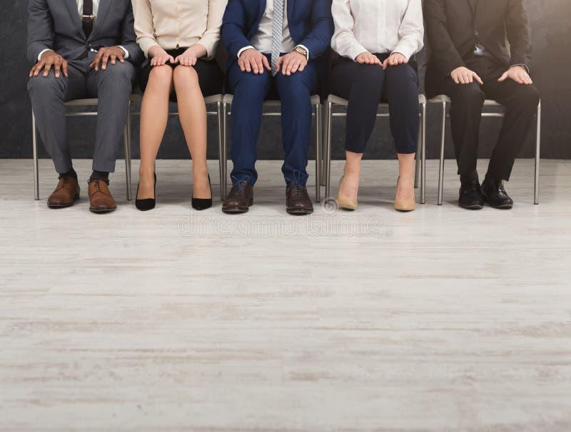 Mensen die met handen op knieën op een rij zitten stock foto