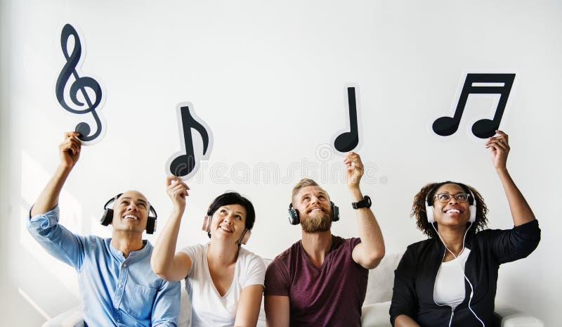 Mensen die muzieknotenpictogrammen houden stock afbeeldingen