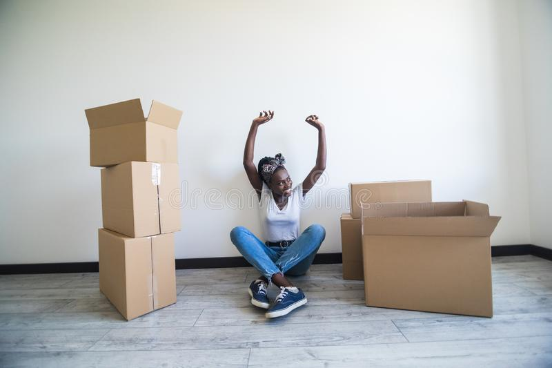 Mensen, die nieuw plaats en reparatieconcept bewegen - gelukkige Afrikaanse Amerikaanse jonge vrouw die met vele kartondozen op v stock afbeelding