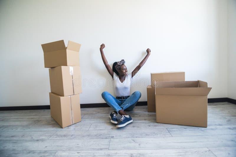 Mensen die, die nieuw plaats en reparatieconcept bewegen - gelukkige Afrikaanse Amerikaanse jonge vrouwenzitting in nieuwe flat e stock foto's