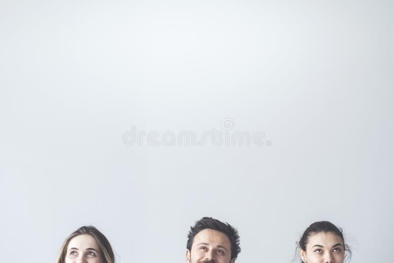 Mensen die omhoog op grijze achtergrond kijken royalty-vrije stock afbeeldingen