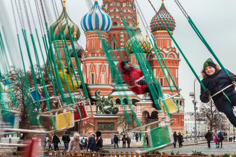 Mensen die op de carrousel op de achtergrond van Pokrovs slingeren stock foto's