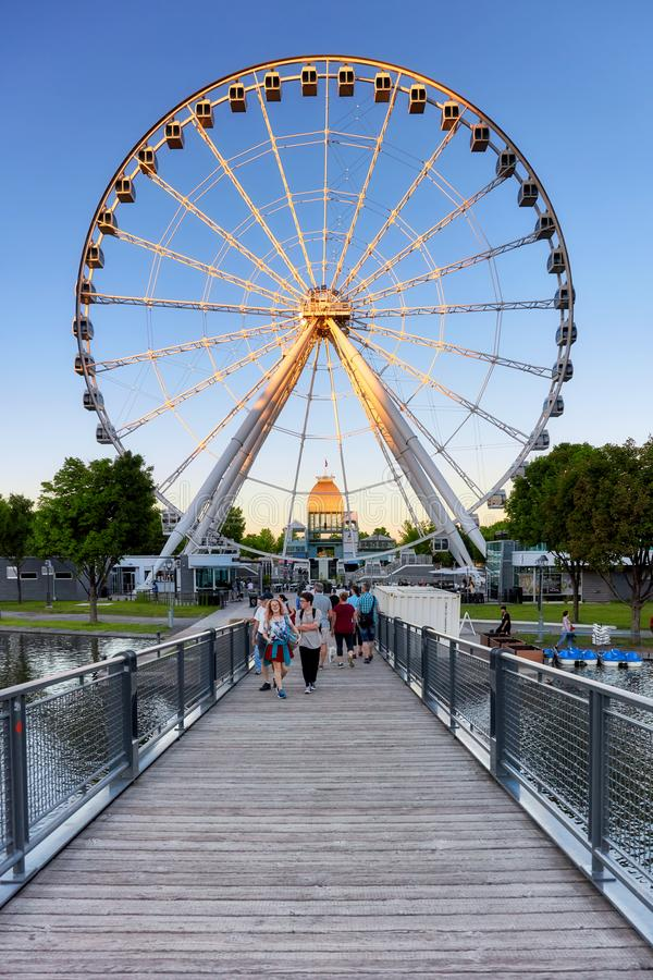 Mensen die op de houten brug in oude haven en Ferris Wheel op de achtergrond op een de zomerdag bij zonsondergang lopen in Montre royalty-vrije stock foto