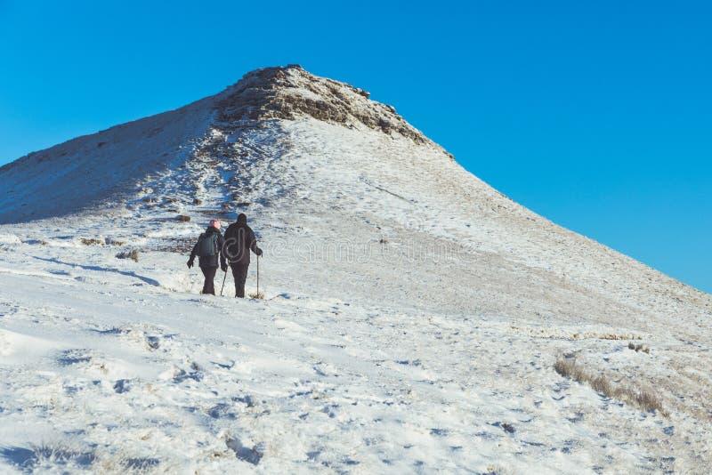 Mensen die op de sneeuw in een bergweg lopen royalty-vrije stock afbeelding