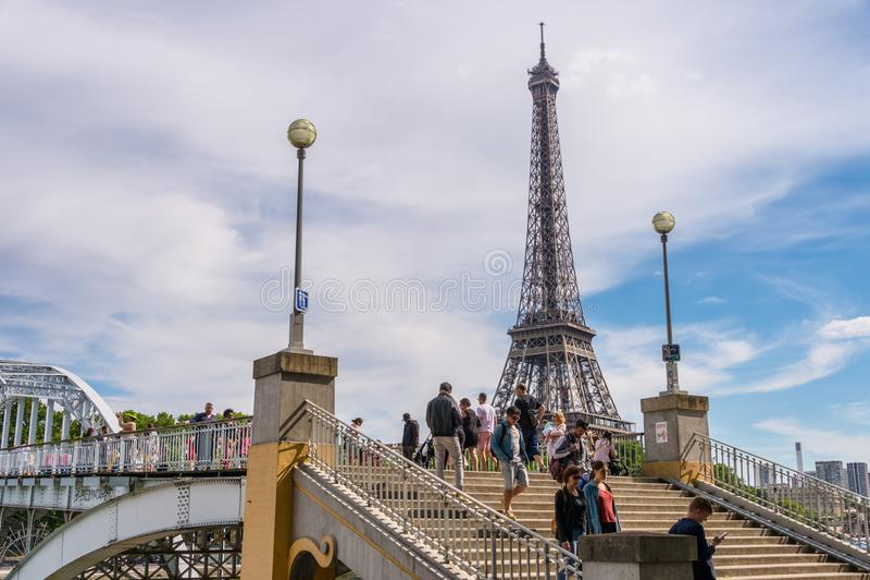 Mensen die op Debilly-Voetgangersbrug met de Toren van Eiffel in de bedelaars lopen stock foto