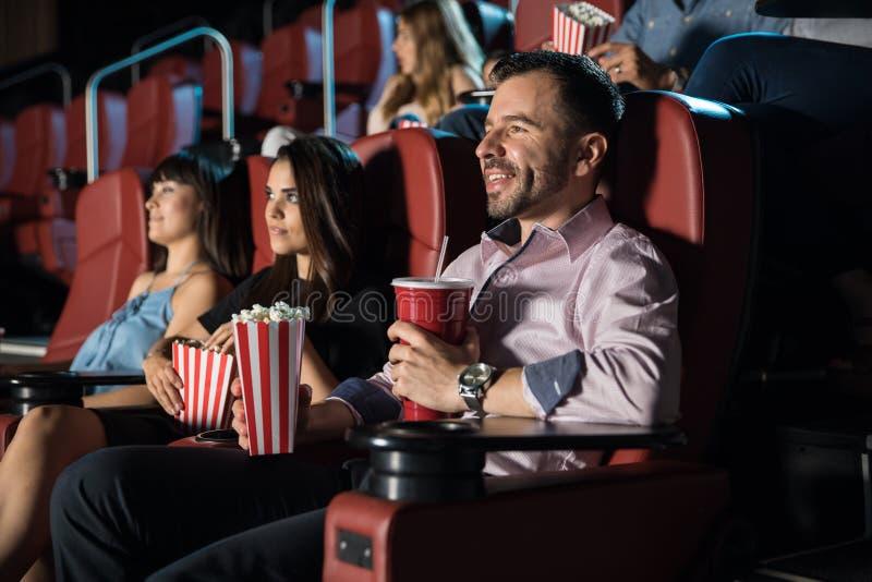 Mensen die op een film letten en popcorn eten stock fotografie