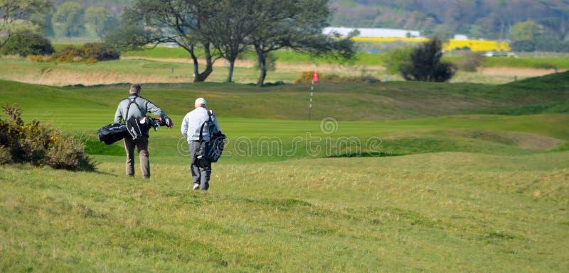 Mensen die op golfcursus naar Speld met golfzakken lopen stock afbeelding