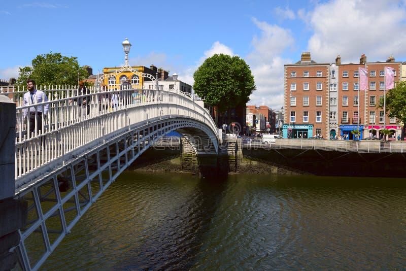 Mensen die op Halfpenny Brug, Liffey-Rivier in Dublin, Ierland gaan stock foto