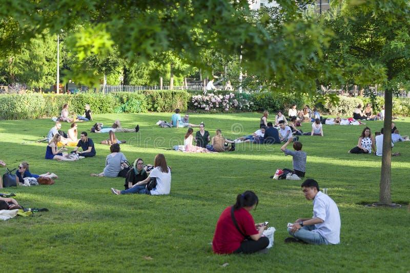 Mensen die op het gazon in het park in het stadscentrum rusten, Londen, het Verenigd Koninkrijk royalty-vrije stock fotografie