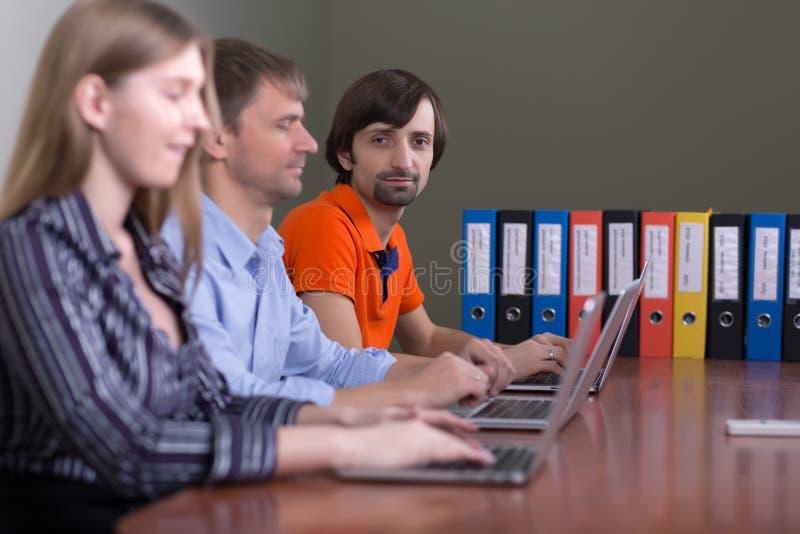 Mensen die op kantoor aan computers werken die in rij zitten stock foto's