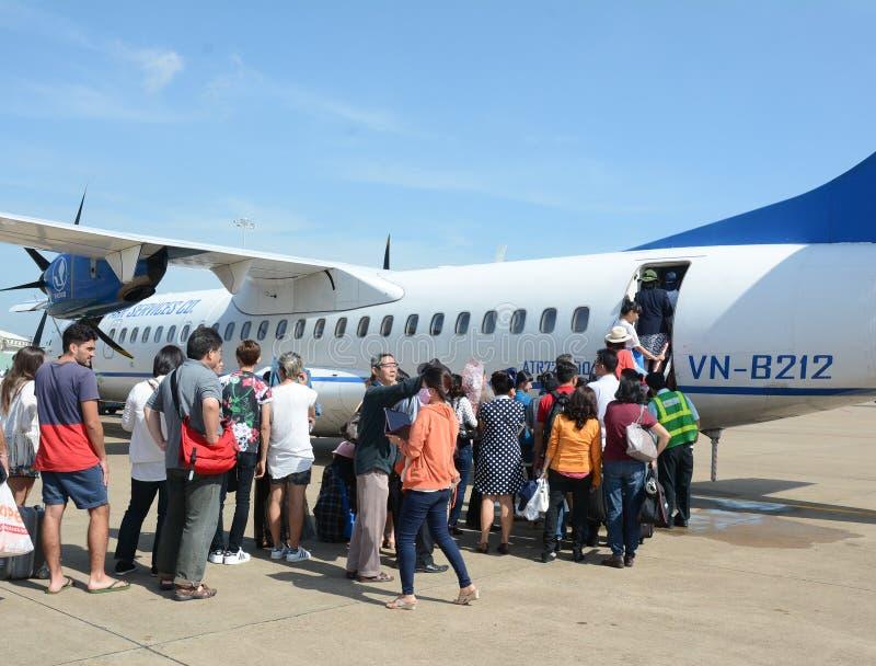 Mensen die op komst aan vliegtuig bij de luchthaven in Nok Ranh, Vietnam wachten stock foto