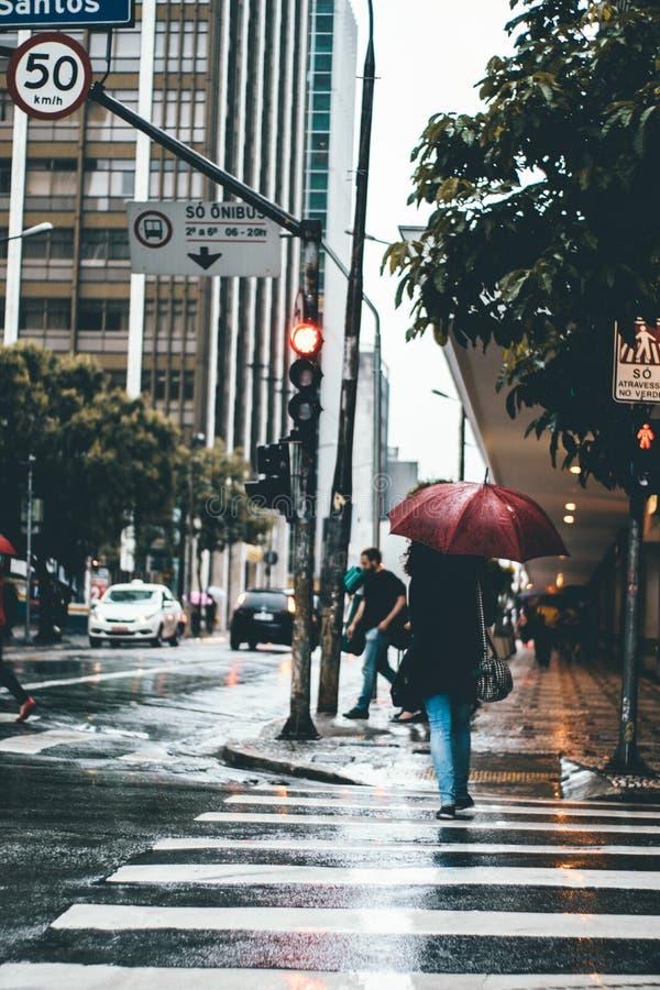 Mensen die op regenachtige stadsstoep lopen stock fotografie