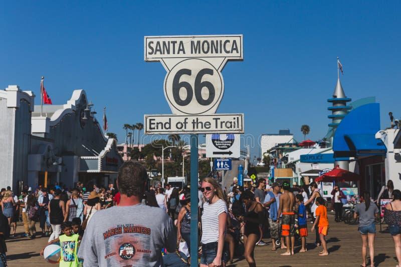 Mensen die op Santa Monica Pier arround het Route 66 -eind van sleepteken lopen stock afbeelding