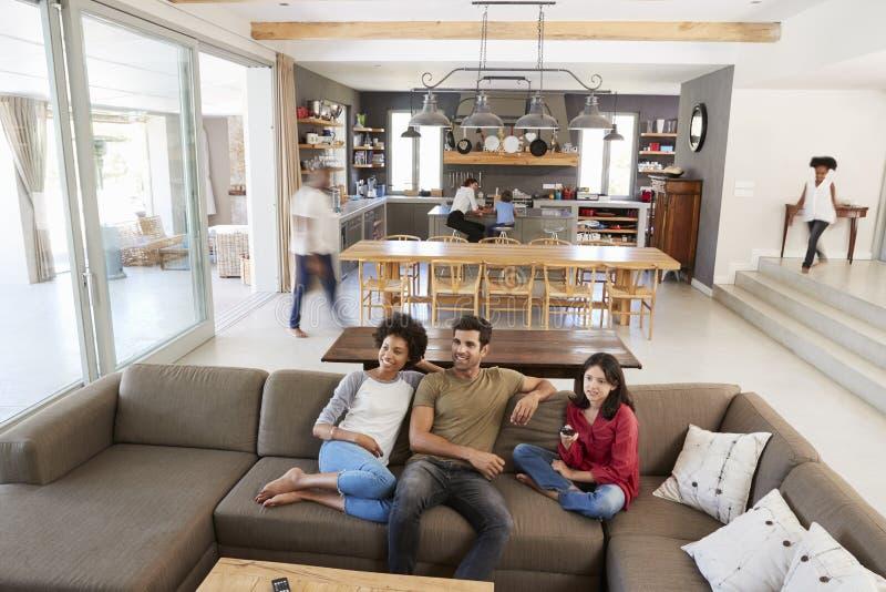 Mensen die op Sofa And Watching-TV in Bezig Familiehuishouden zitten royalty-vrije stock foto