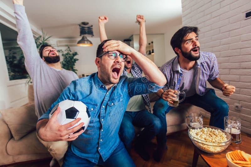 Mensen die op sport bij vrolijk gillen van TV letten samen thuis royalty-vrije stock fotografie