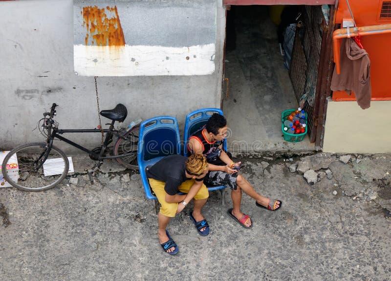 Mensen die op straat in Manilla, Filippijnen zitten stock fotografie