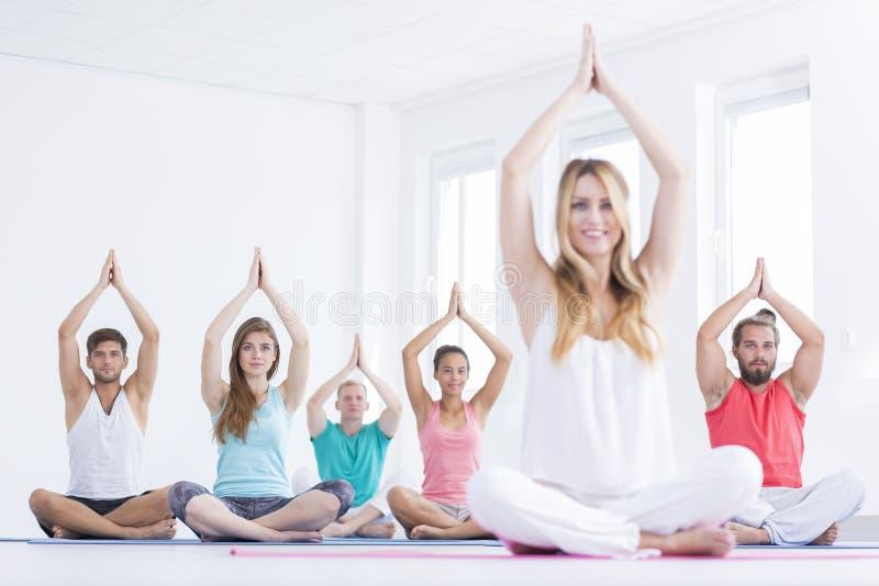 Mensen die op yogamatten zitten stock afbeeldingen