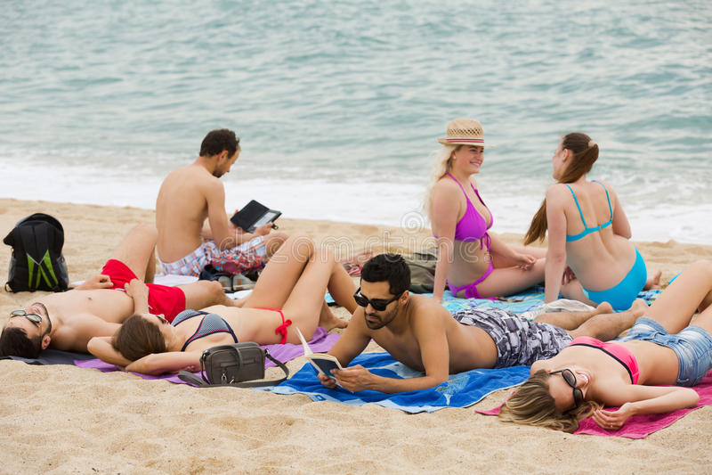 Mensen die op zand bij strand leggen stock fotografie