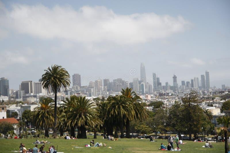 Mensen die in Opdracht Dolores Park met de mening van wolkenkrabbers van San Francisco rusten stock afbeelding