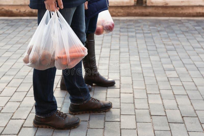Mensen die plastic zakken met producten, close-up dragen Ruimte voor tekst stock foto
