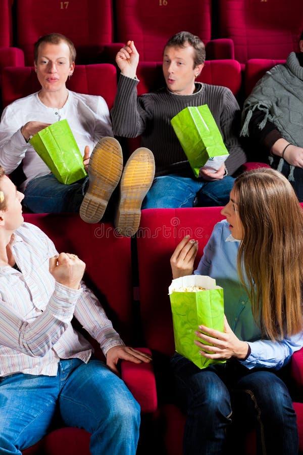Mensen die popcorn in theater eten stock afbeelding