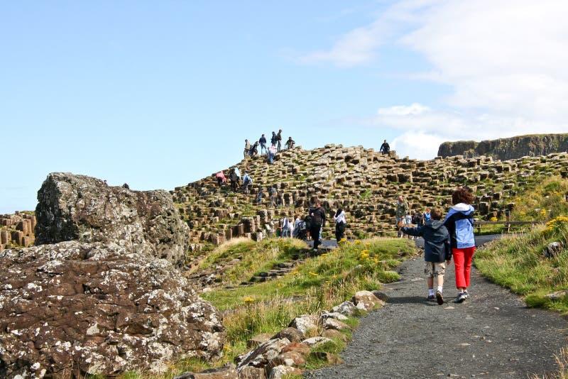 Mensen die rond Reuzenverhoogde weg en Klippen, Noord-Ierland lopen royalty-vrije stock afbeeldingen