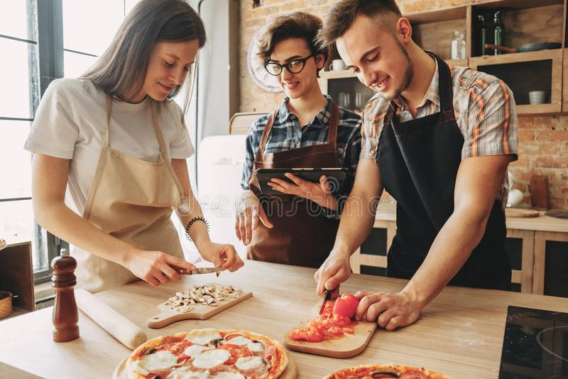 Mensen die samen koken Bedrijf van vrienden die ingrediënten hakken stock afbeelding