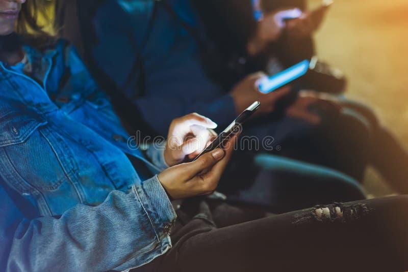 Mensen die samen vinger op het schermsmartphone de richten op achtergrond bokeh licht in nacht atmosferische stad, groeperen volw royalty-vrije stock foto