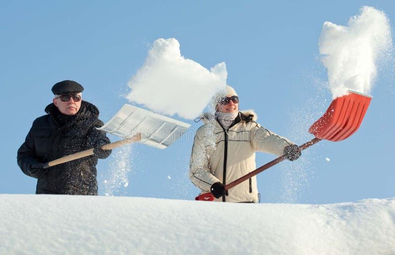Mensen die sneeuw op een dak scheppen royalty-vrije stock afbeelding