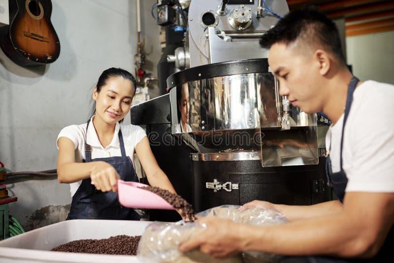 Mensen die in team aan koffiefabriek werken stock afbeelding