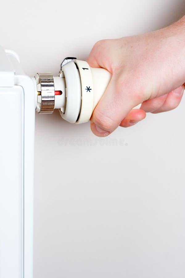 Mensen die thermostaat op huisradiator aanpassen stock foto's