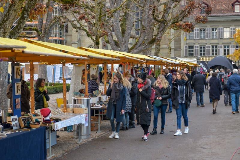 Mensen die traditionele Kerstmismarkt bezoeken dichtbij cathedra van Bern stock afbeeldingen