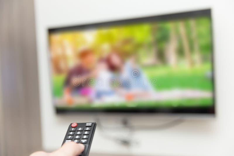 Mensen die TV-op hand met afstandsbediening letten stock afbeeldingen