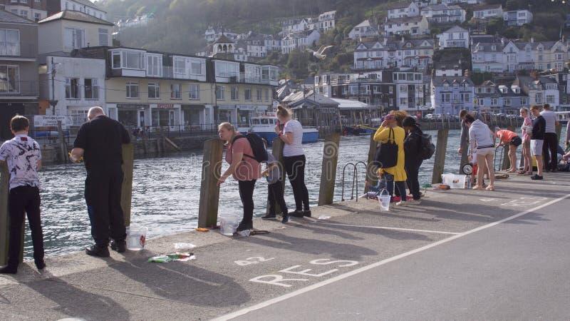 Mensen die van één of andere krab genieten die van het havenoosten Looe vissen, Cornwall, het UK royalty-vrije stock afbeeldingen