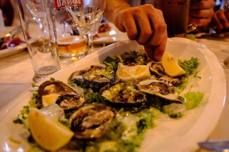 Mensen die van een plaat van gekookte oesters eten stock foto's