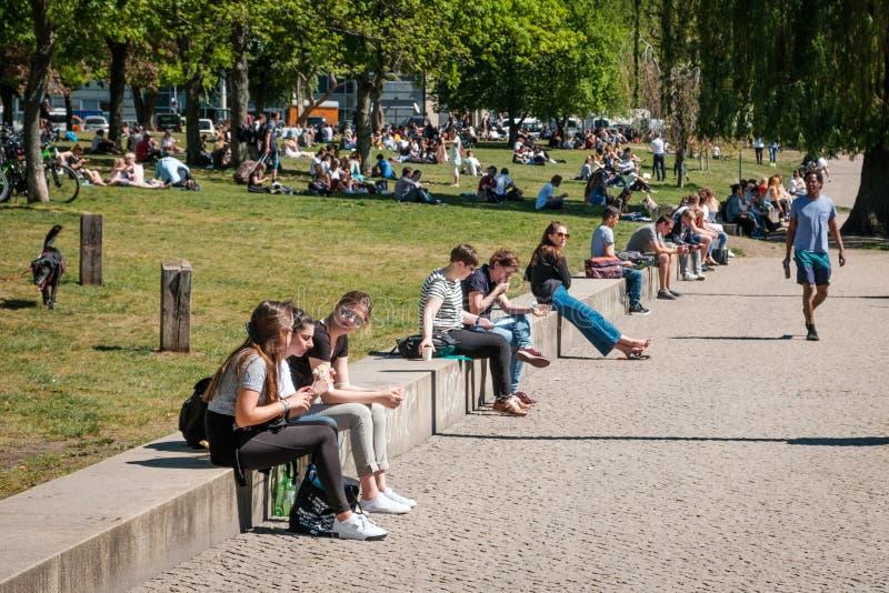 Mensen die van zonnig weer in openbaar park genieten en openlucht op straat royalty-vrije stock afbeelding