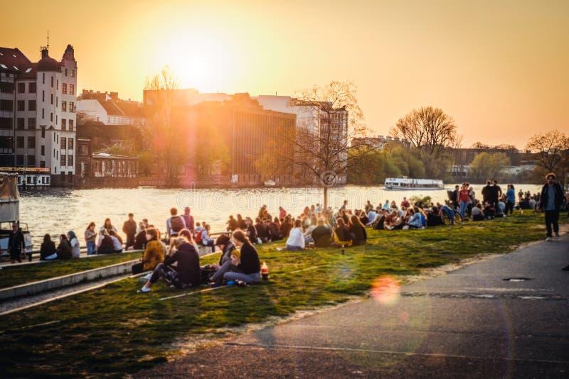 Mensen die van zonsondergang bij rivier naast Berlin Wall/East Side Gallery in Berlijn, Duitsland genieten stock afbeelding