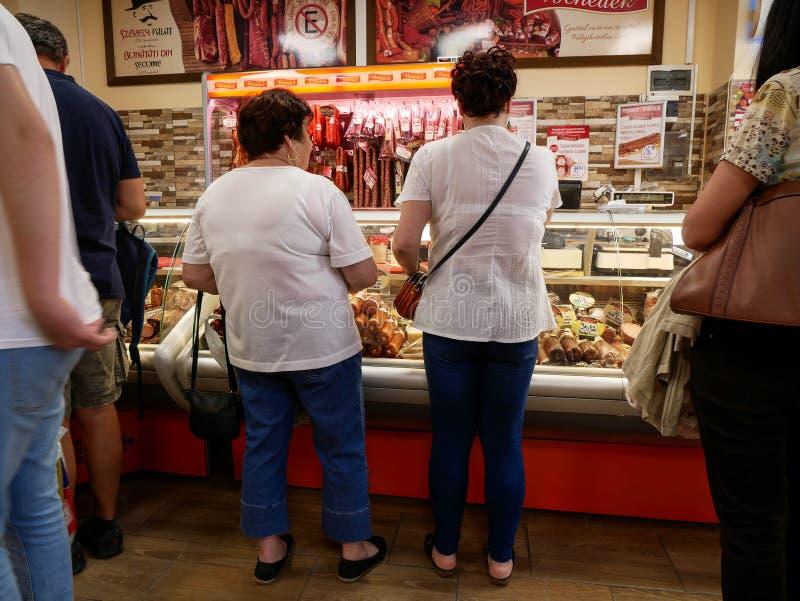 Mensen die vleeswaren kopen bij de opslag van de lokale slager stock foto