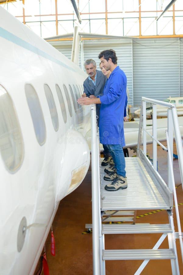 Mensen die vliegtuigenfuselage bestuderen royalty-vrije stock afbeeldingen