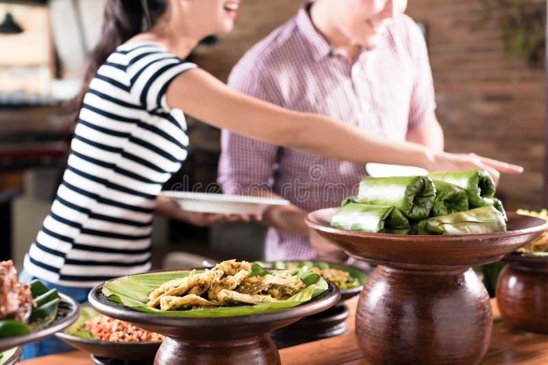 Mensen die voedsel kiezen bij Indonesisch buffet in restaurant stock afbeelding