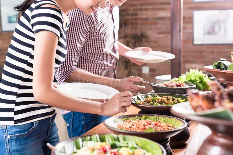 Mensen die voedsel kiezen bij Indonesisch buffet in restaurant stock fotografie