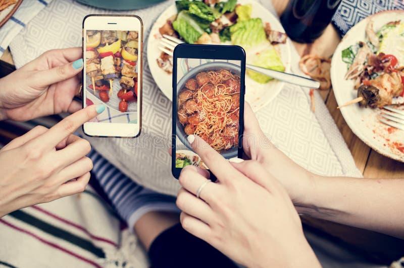 Mensen die voedselfoto's op mobiele telefoon delen stock afbeelding