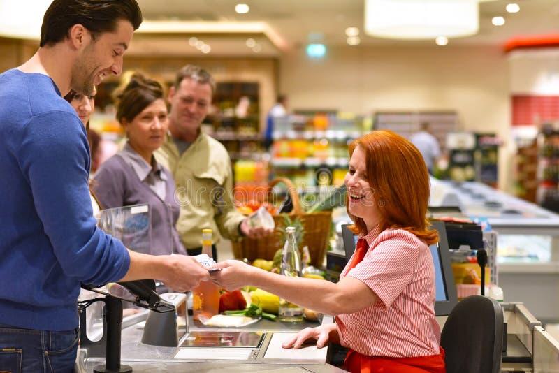 Mensen die voor voedsel in de supermarkt winkelen - controle het betalen royalty-vrije stock afbeelding