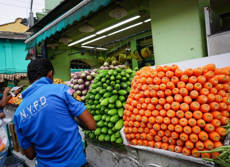 Mensen die vruchten en groenten verkopen bij straatmarkt in Weinig India, Singapore stock foto