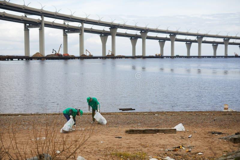 Mensen die vuilnis op kust plukken royalty-vrije stock afbeeldingen