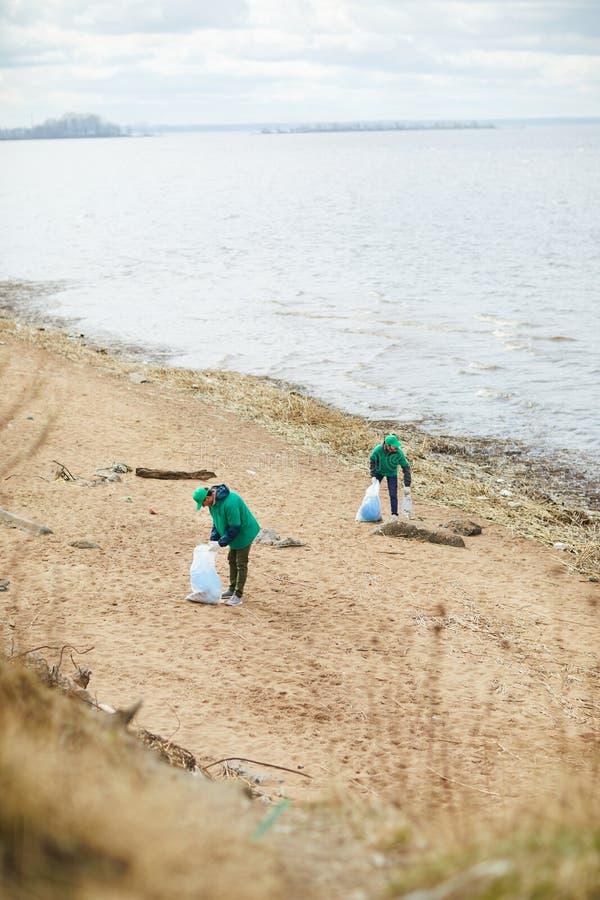 Mensen die vuilnis op kust verzamelen royalty-vrije stock afbeeldingen