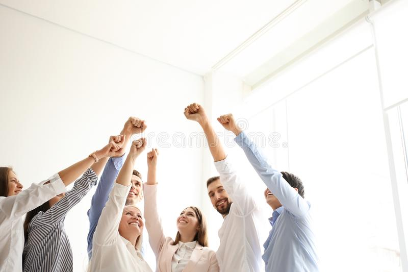 Mensen die vuisten samen binnen opheffen royalty-vrije stock afbeelding