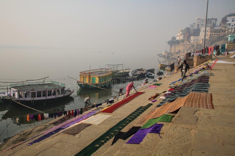 Mensen die wasserij vroege ochtend op ganga ghats in Varanasi, Uttar Pradesh, India schoonmaken royalty-vrije stock afbeelding