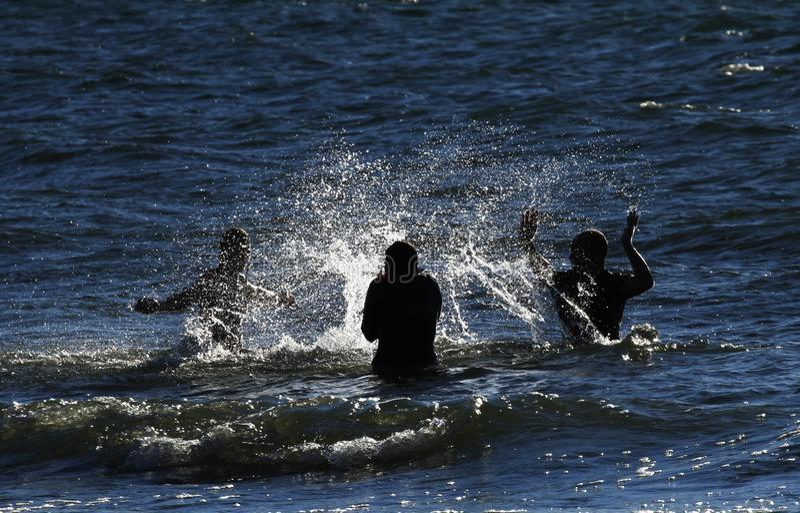 Mensen die water tegen elkaar in het overzees in Gotland, Zweden bespatten stock foto